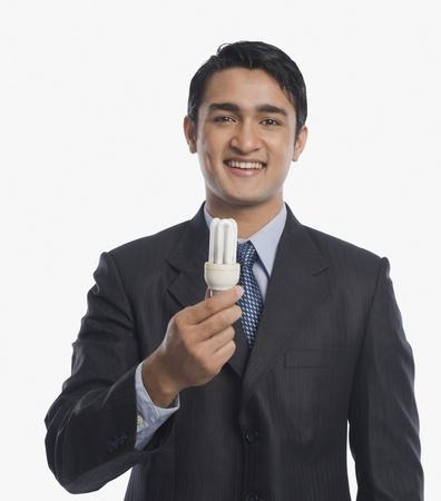 Businessman holding a CFL bulb