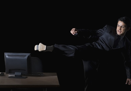 Frustrated businessman kicking a desktop pc Stock Photo - 10166749
