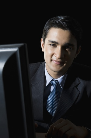 Businessman sitting in front of a desktop pc and smiling Stock Photo - 10168698