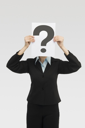 Businesswoman holding a card with question mark in front of a face Stock Photo - 10166874