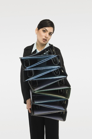 futility: Businesswoman holding stack of binders