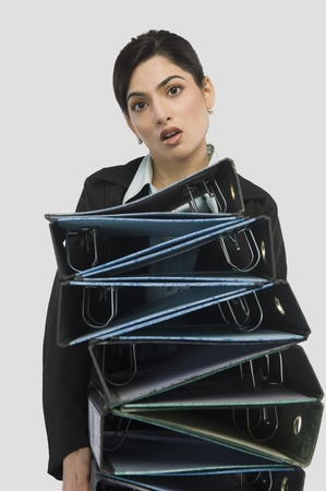 chaos: Businesswoman holding stack of binders