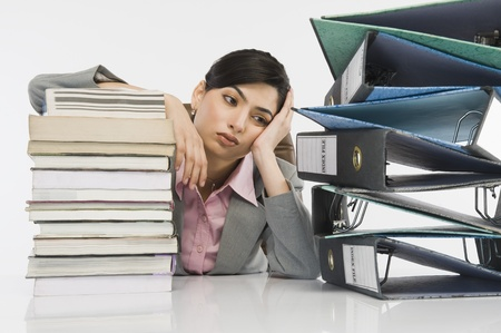 drudgery: Stack of books in front of a businesswoman at desk