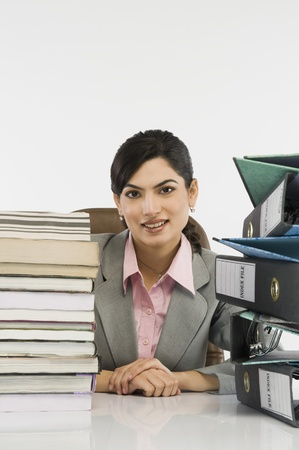 front desk: Stack of books and binders in front of a businesswoman at desk