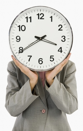 clock: Businesswoman hiding her face with a clock LANG_EVOIMAGES