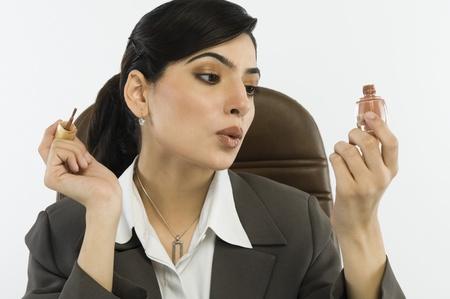 オフィスで指の爪の爪塗料を塗布する実業家
