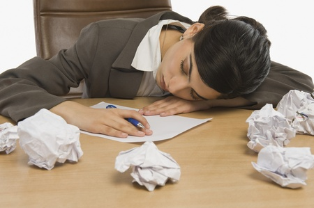 office physical pressure paper: Businesswoman sleeping at desk LANG_EVOIMAGES