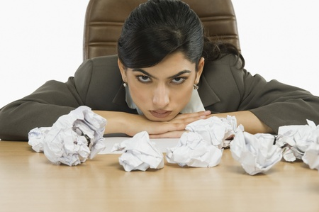 Businesswoman staring crumpled papers on her desk Stock Photo - 10167390