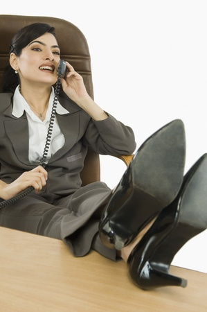 feet on desk: Businesswoman talking on the telephone in an office