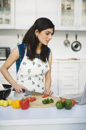 Woman cooking with the recipe on a laptop Stock Photo - 10167191
