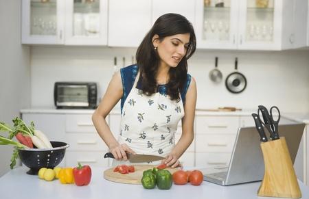 랩톱에서 제조법으로 요리하는 여자