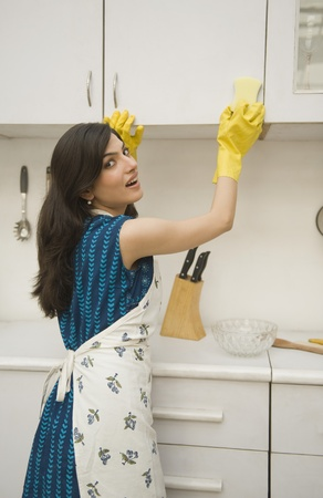 Woman cleaning a kitchen cabinet with a sponge