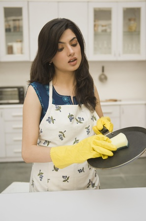 Woman cleaning a griddle with a sponge