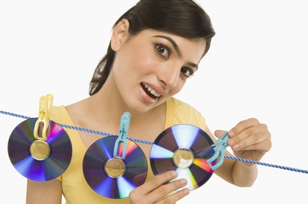 Woman hanging CDs on a clothesline Stock Photo - 10168526