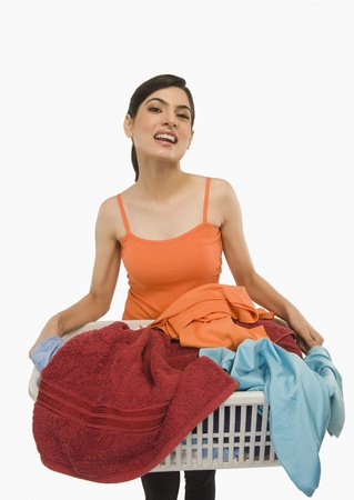 Woman holding laundry basket filled with clothing Stock Photo - 10167475