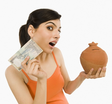 curren: Woman holding Indian currency notes with a piggy bank