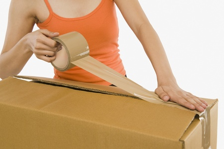 packing tape: Woman packing cardboard by packing tape