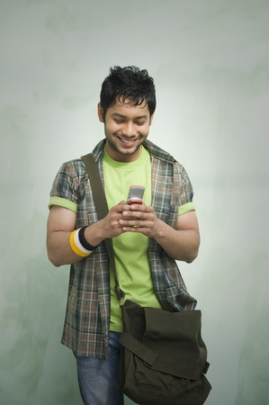 University student text messaging on a mobile phone and smiling Stock Photo - 10168168