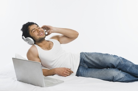 Man listening to headphones with a laptop