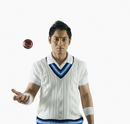 Portrait of a cricket bowler tossing a ball
