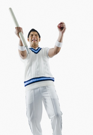 Cricket bowler cheering with a cricket ball and stump Stock Photo - 10166832