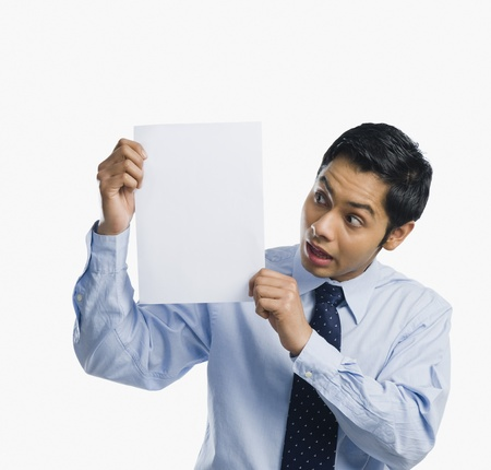 white sheet: Businessman showing a sheet of blank paper and looking shocked