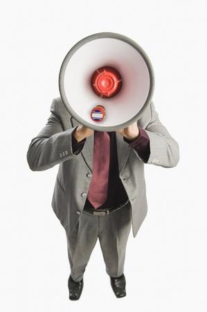loudspeaker: Businessman holding a megaphone