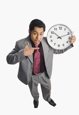 Businessman showing a clock Stock Photo