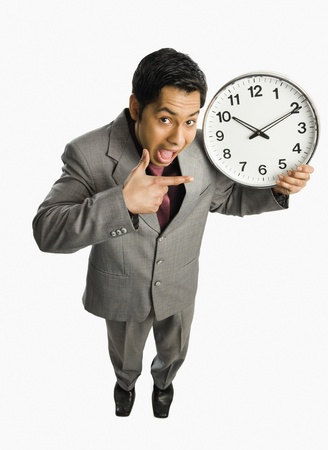 getting late: Businessman showing a clock LANG_EVOIMAGES