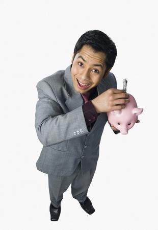 Businessman putting money into a piggy bank Stock Photo - 10168408
