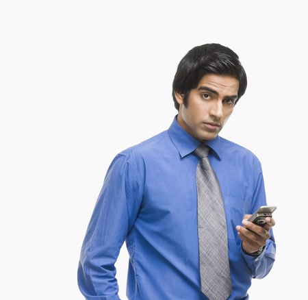 clipping  messaging: Portrait of a businessman text messaging on a mobile phone