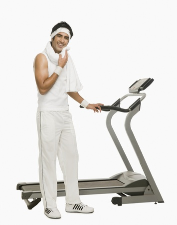 self conscious: Man wiping his face with a towel beside a treadmill