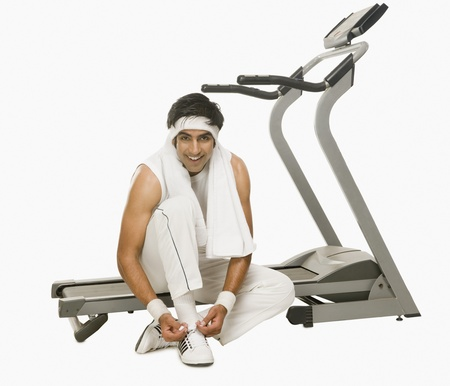 Man sitting on a treadmill and tying shoelaces Stock Photo - 10168889