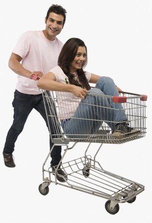 humo: Man pushing a woman sitting in shopping cart