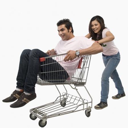 humo: Woman pushing a man sitting in shopping cart