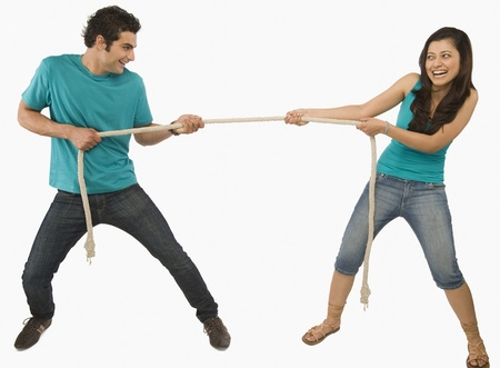 battle of the sexes: Young couple playing tug of war