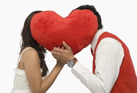 Couple romancing behind a heart shape Stock Photo