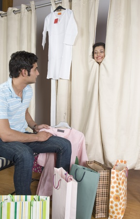 fitting room: Man looking at a woman peeking out of a fitting room