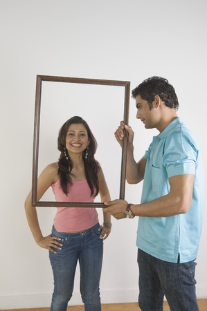 gurgaon: Man holding a picture frame in front of a woman