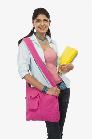 shoulder bag: Female university student holding books and day dreaming