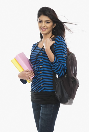 Female university student holding books and smiling Stock Photo - 10168098