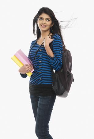 Female university student holding books and smiling