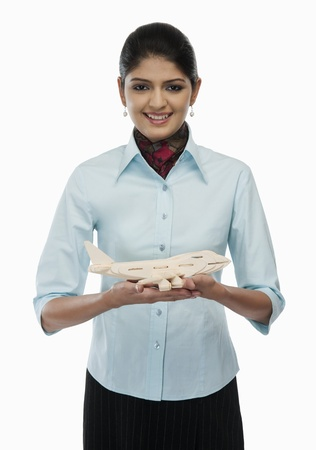 Female flight attendant holding a toy airplane Stock Photo - 10168658