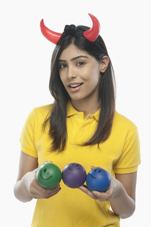 Portrait of a woman wearing devil's horns and holding smiley face balls Stock Photo - 10167974