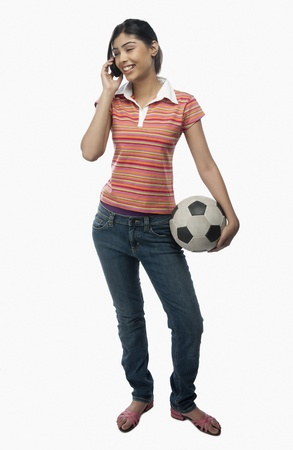 Woman talking on a mobile phone and holding a soccer ball Stock Photo - 10166960