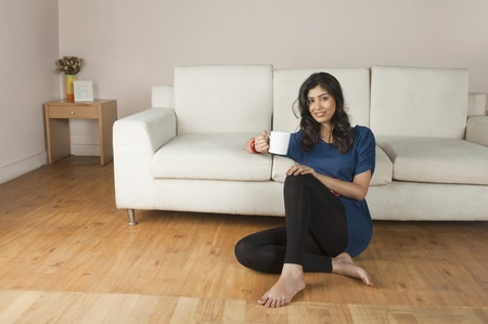 wood flooring: Woman holding a cup of coffee and smiling