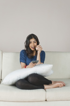 woman on couch: Woman holding a cricket ball and operating a remote control LANG_EVOIMAGES