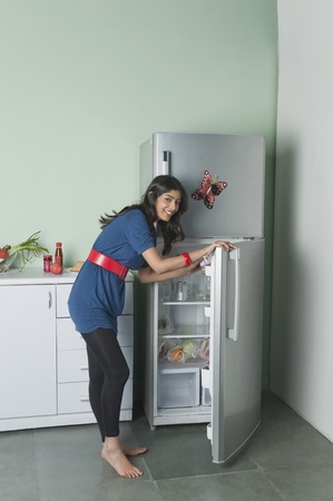 Portrait of a woman opening a refrigerator Stock Photo - 10168419