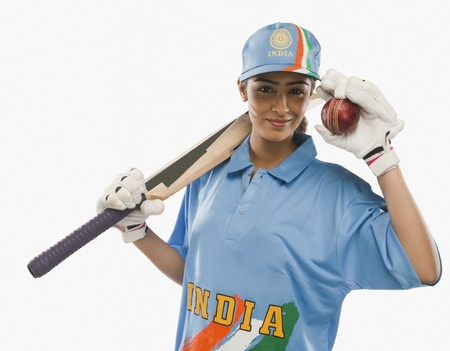 cricket bat: Portrait of a female cricketer holding a cricket bat and a ball
