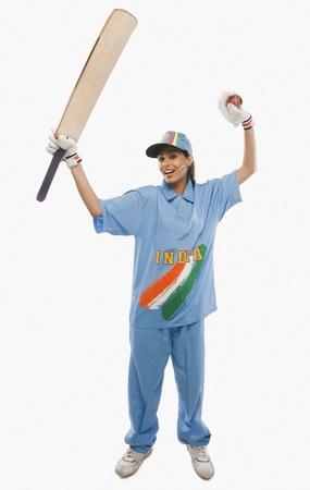 triumphing: Female cricketer raising bat in celebration